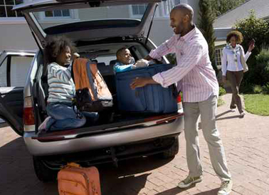 Son and daughter (6-10) helping father load luggage in back of c